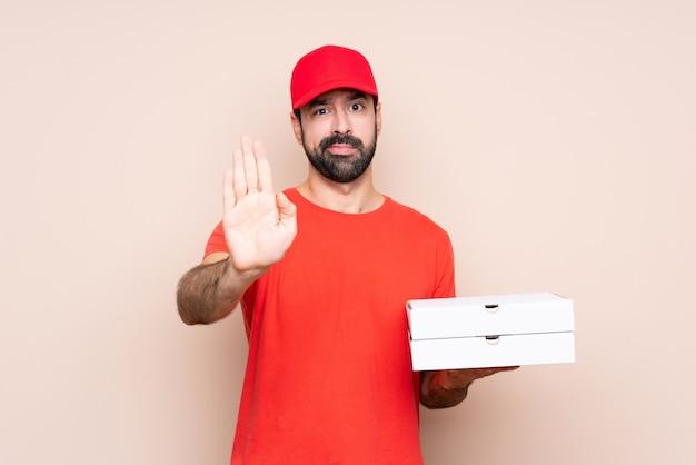 Junger mann, der eine pizza über der lokalisierten wand macht endgeste hält