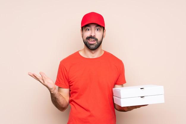 Junger mann, der eine pizza über der lokalisierten wand macht zweifel hält, gestikulieren