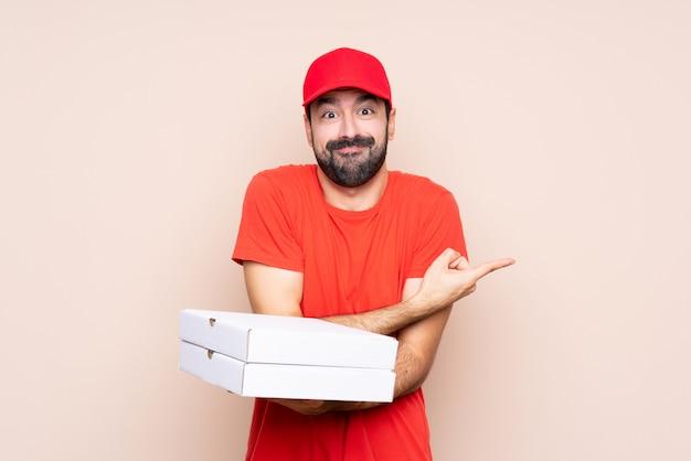 Junger mann, der eine pizza über der lokalisierten wand zeigt auf die seitenteile hat zweifel hält