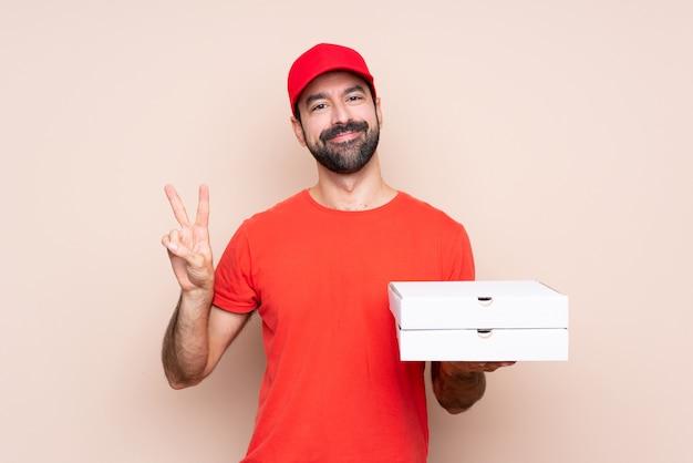Junger mann, der eine pizza über der lokalisierten wand zeigt siegeszeichen mit beiden händen hält