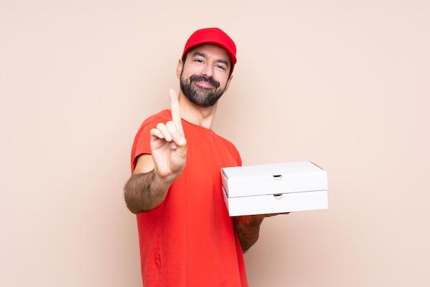 Junger mann, der eine pizza über der lokalisierten wand zeigt und anhebt einen finger hält