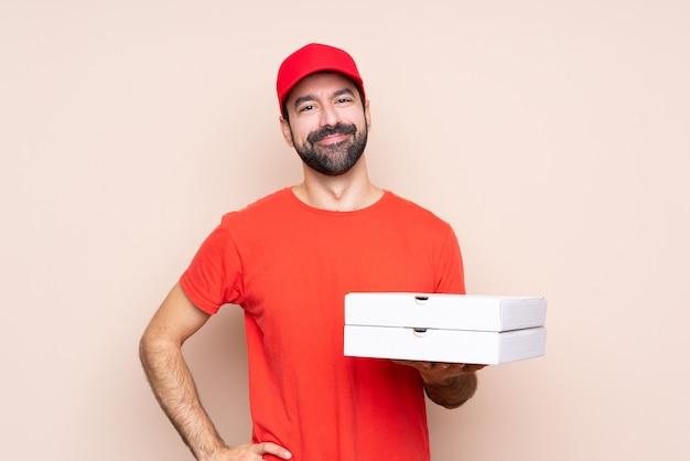 Junger mann, der eine pizza über getrenntem lächeln anhält