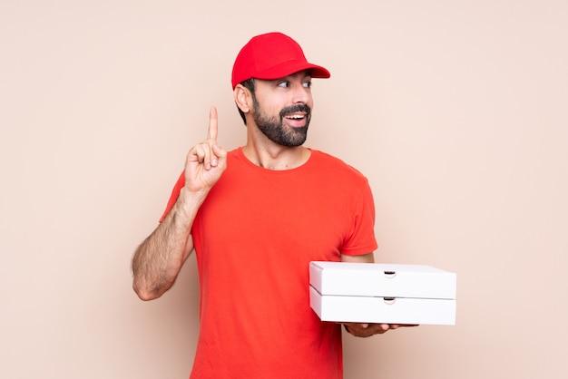 Junger mann, der eine pizza über lokalisiertem denken eine idee oben zeigt den finger hält