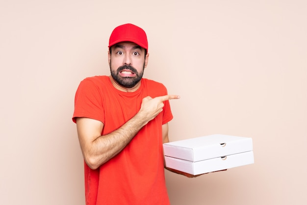 Junger mann, der eine pizza über lokalisiertem erschrockenem hält und auf die seite zeigt
