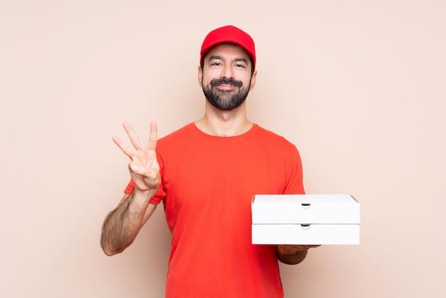Junger mann, der eine pizza über lokalisiertem hintergrund glücklich hält und drei mit den fingern zählt