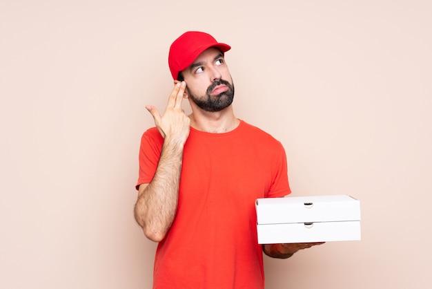 Junger mann, der eine pizza über lokalisiertem hintergrund mit den problemen machen selbstmordgeste hält