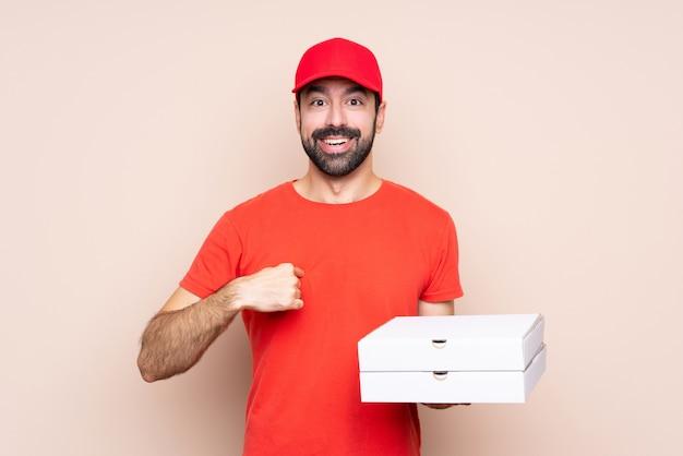 Junger mann, der eine pizza über lokalisiertem hintergrund mit überraschungsgesichtsausdruck hält