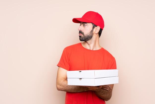 Junger mann, der eine pizza über lokalisiertem hintergrundporträt hält