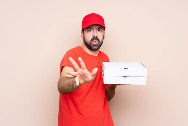 Junger mann, der eine pizza über lokalisierten nervösen ausdehnenden händen zur front hält