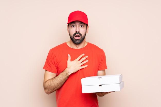 Junger mann, der eine pizza über lokalisierter wand beim schauen überrascht und entsetzt hält
