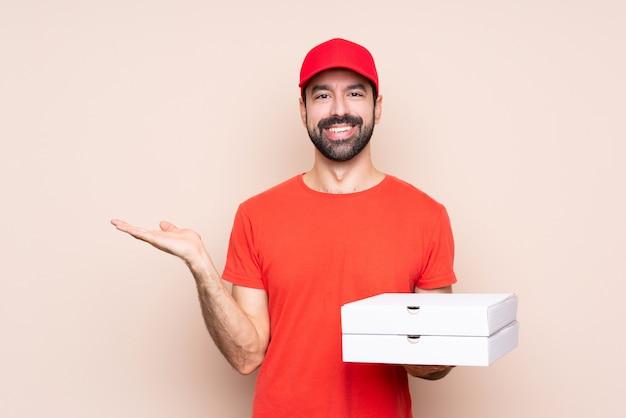 Junger mann, der eine pizza über lokalisierter wand hält copyspace eingebildet auf der palme hält, um eine anzeige einzufügen