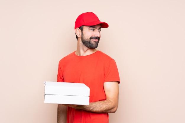 Junger mann, der eine pizza über lokalisierter wand mit den armen gekreuzt und glücklich hält