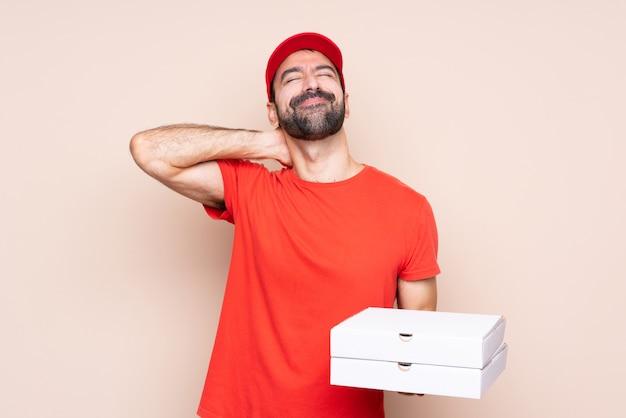 Junger mann, der eine pizza über lokalisierter wand mit halsschmerzen hält