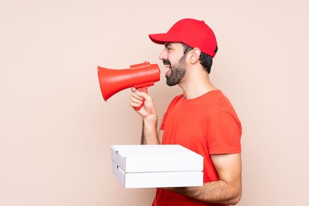 Junger mann, der eine pizza über lokalisierter wand schreit durch ein megaphon hält