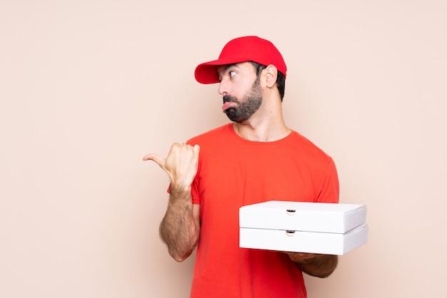 Junger mann, der eine pizza über lokalisierter wand unglücklich hält und auf die seite zeigt