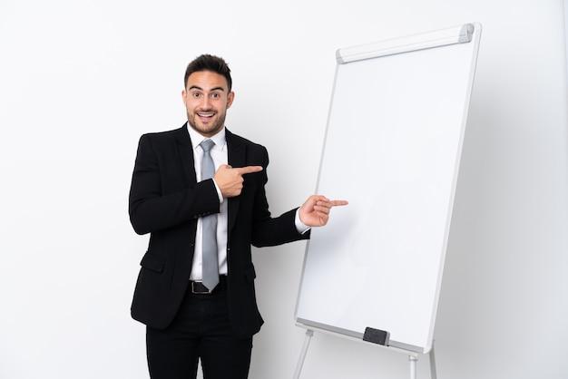 Junger mann, der eine präsentation auf weißer tafel gibt und überrascht ist, während er seite zeigt