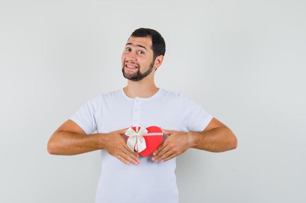 Junger mann, der eine rote geschenkbox im weißen t-shirt hält und urkomisch aussieht, vorderansicht.