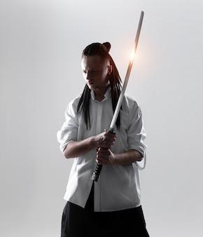 Junger mann, der eine samuraiklinge hält. zauberfoto.