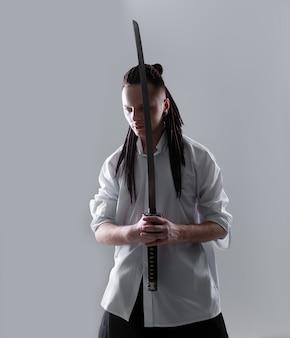 Junger mann, der eine samuraiklinge hält.