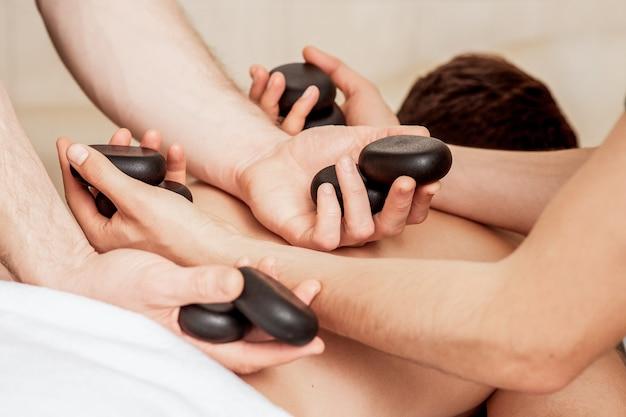 Junger mann, der eine steinmassage auf dem rücken erhält, während hände des massagetherapeuten steine auf ihren rücken legen.