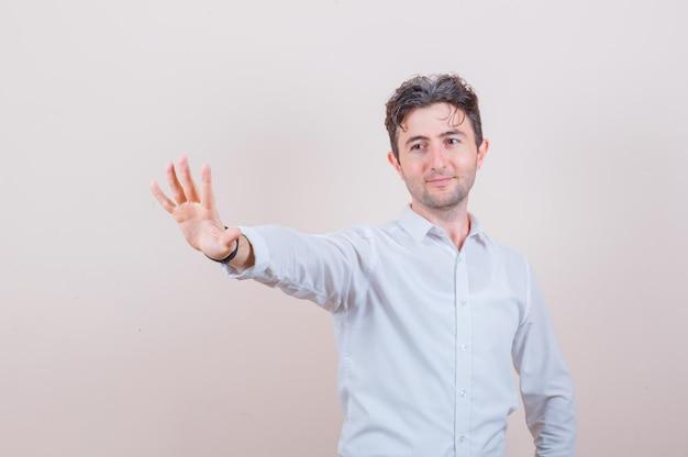 Junger mann, der eine stopp-geste im weißen hemd zeigt und fröhlich aussieht