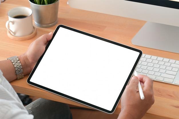 Junger mann, der eine tablette im büroarbeitsplatz verwendet