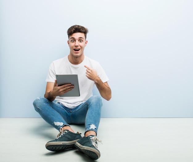 Junger mann, der eine tablette sitzt, überraschte das zeigen auf und breit lächelte.