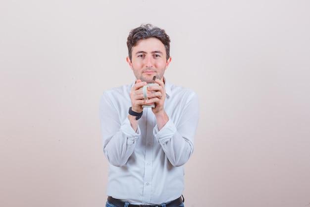 Junger mann, der eine tasse getränk hält und in weißem hemd, jeans lächelt