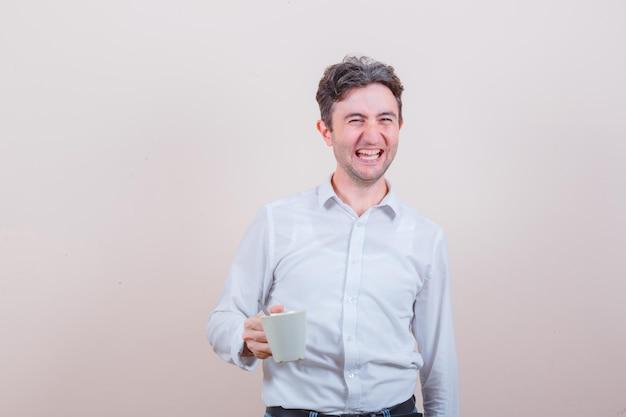 Junger mann, der eine tasse getränk in weißem hemd, jeans hält und glücklich aussieht