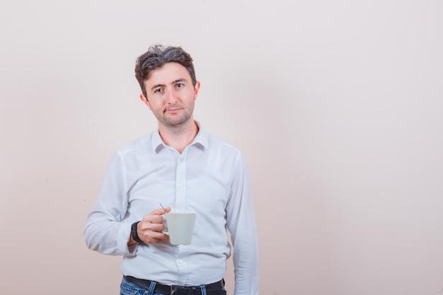 Junger mann, der eine tasse getränk in weißem hemd, jeans und nachdenklichem blick hält