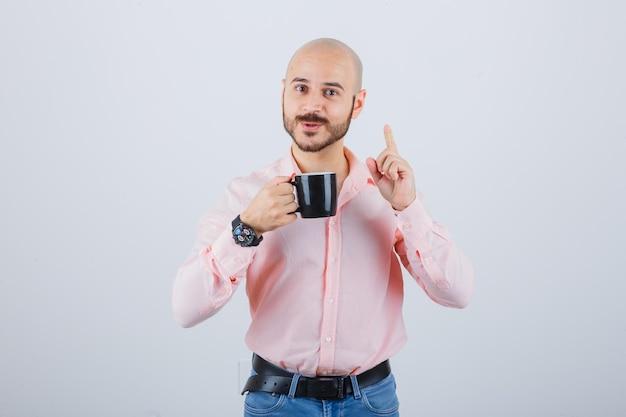 Junger mann, der eine tasse hält, während er in rosa hemd, jeans, vorderansicht nach oben zeigt.