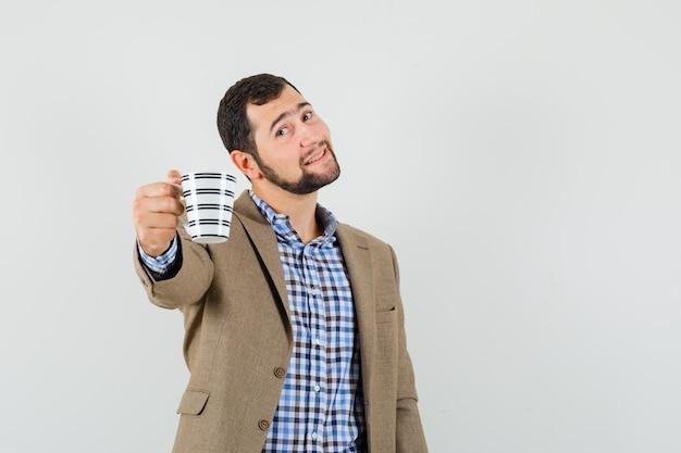 Junger mann, der eine tasse kaffee in hemd, jacke anbietet und sanft aussieht. vorderansicht.