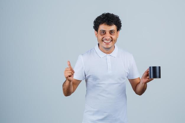 Junger mann, der eine tasse tee hält, während er den daumen in weißem t-shirt und jeans zeigt und glücklich aussieht. vorderansicht.