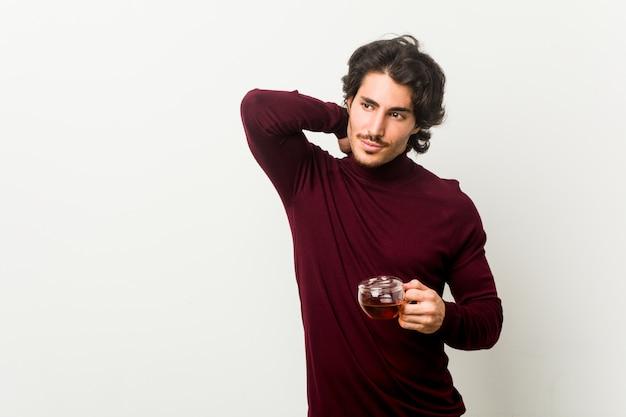 Junger mann, der eine teeschale berührt zurück vom kopf hält, eine wahl denkt und trifft.