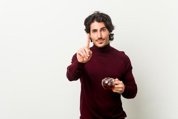 Junger mann, der eine teetasse hält, die nummer eins mit finger zeigt.