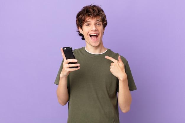 Junger mann, der eine zelle hält, sich glücklich fühlt und mit aufgeregter aufregung auf sich selbst zeigt