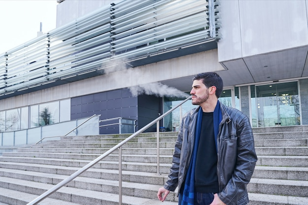Junger mann, der eine zigarette vor einer öffentlichen bibliothek auf einer messe morgen winter raucht. konzept der schlechten gewohnheiten