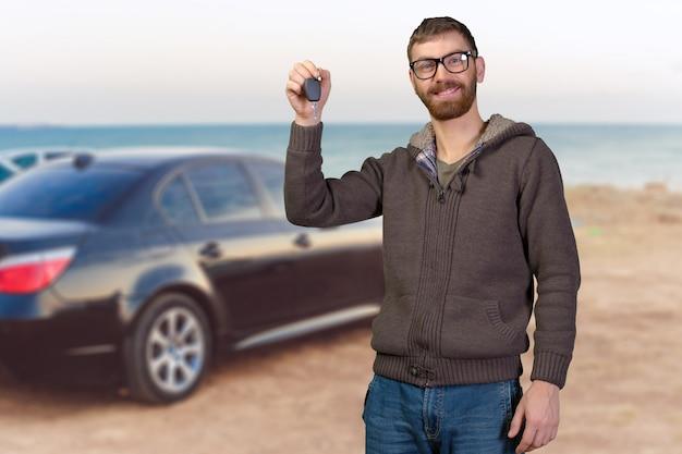 Junger mann, der einen autoschlüssel hält