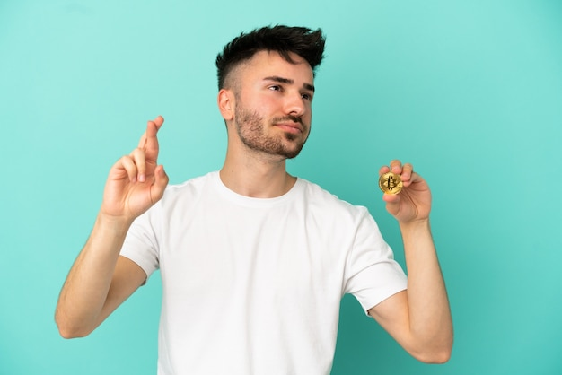 Junger mann, der einen bitcoin auf blauem hintergrund mit gekreuzten fingern hält und das beste wünscht
