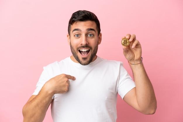 Junger mann, der einen bitcoin isoliert auf rosa hintergrund mit überraschendem gesichtsausdruck hält