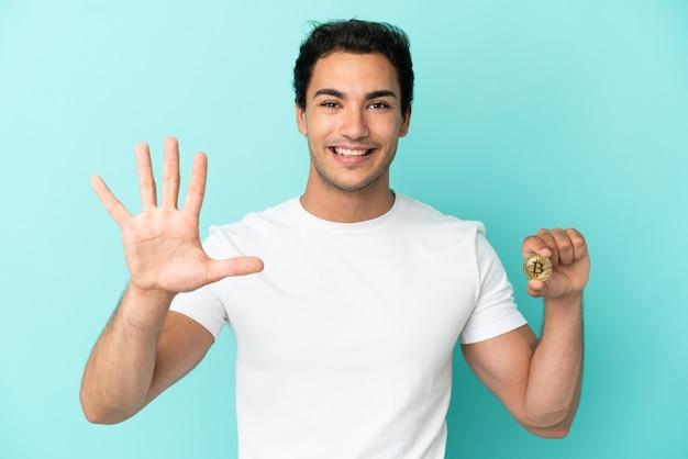 Junger mann, der einen bitcoin über isoliertem blauem hintergrund hält und mit den fingern fünf zählt