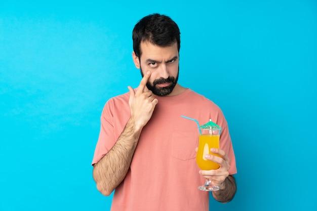 Junger mann, der einen cocktail über blau hält, der etwas zeigt