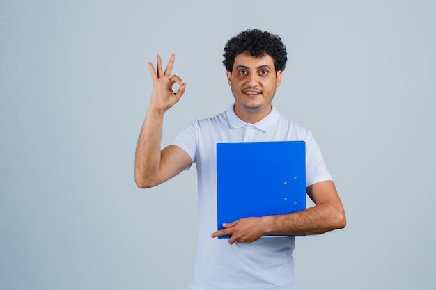 Junger mann, der einen dateiordner hält und ein ok-zeichen in weißem t-shirt und jeans zeigt und glücklich aussieht, vorderansicht.