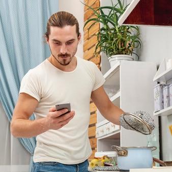 Junger mann, der einen deckeltopf hält und telefon betrachtet