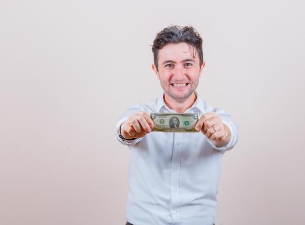 Junger mann, der einen dollarschein im weißen hemd hält und glücklich aussieht