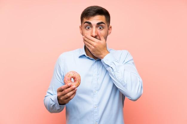 Junger mann, der einen donut über lokalisierter rosa wand mit überraschungsgesichtsausdruck hält