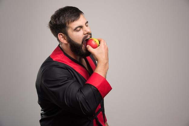 Junger mann, der einen frischen apfel isst.