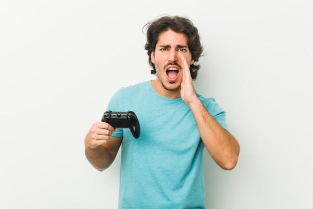 Junger mann, der einen gamecontroller hält, der aufgeregt nach vorne schreit.