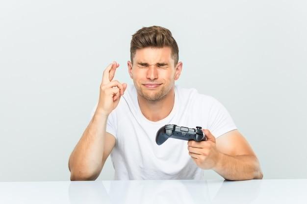 Junger mann, der einen gamecontroller hält, der finger für glück kreuzt