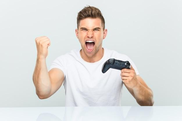 Junger mann, der einen gamecontroller hält, der sorglos und aufgeregt jubelt